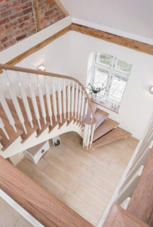 A staircase with a turn at the end and oak treads and handrail finished with Oil Plus 2C wood finish.