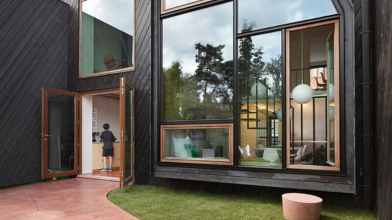 A boy walking into the wide open front french doors of a masterfully designed city home.