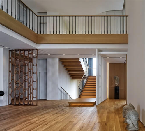 Natural looking hardwood floors with a staircase with accent lighting in a house with white walls.