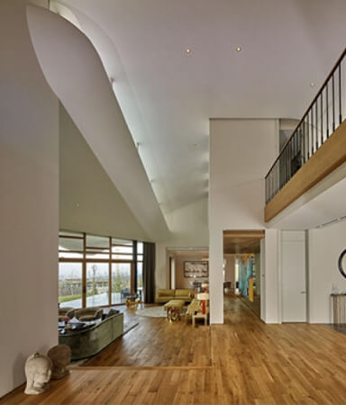 Hardwood flooring in a living area and high curved ceiling accents.