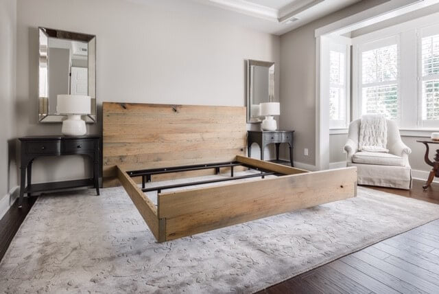 American Wormy Chestnut bed-frame in a master bedroom without mattress on it.