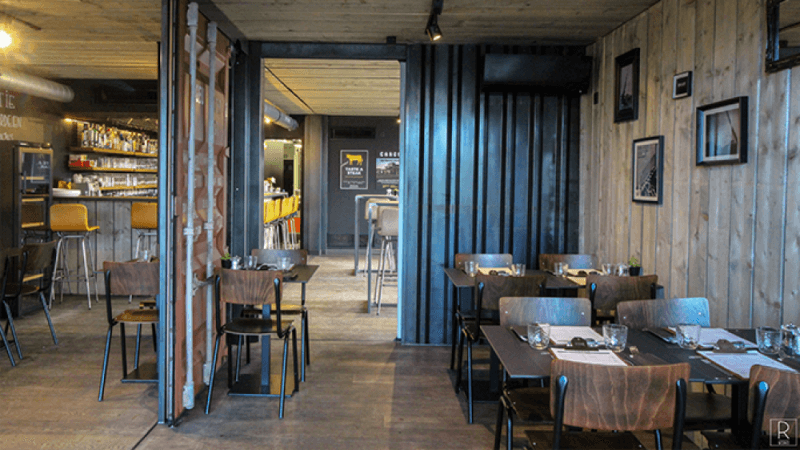 A pop-up restaurant made from shipping containers containers tables, decor, and wood flooring finished with Rubio Monocoat hardwax oil wood finishes.