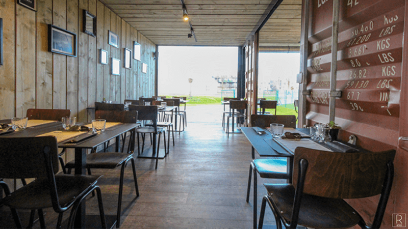 A restaurant patio area made from shipping containers with a wood floor.