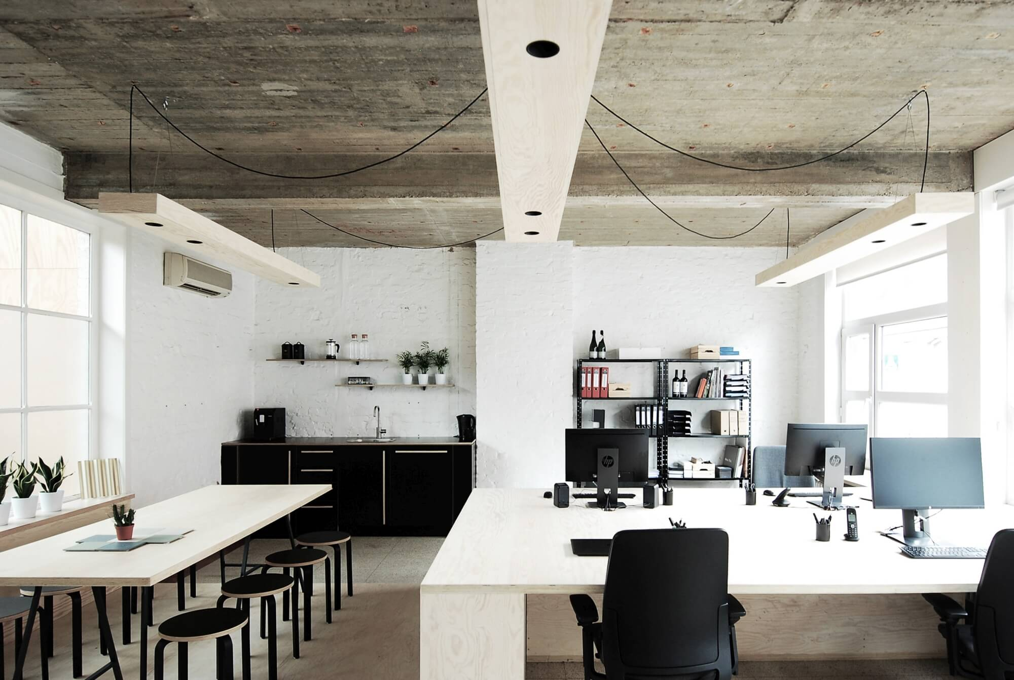 Architectural offices with white bricks, grey ceiling, and light plywood accents throughout.