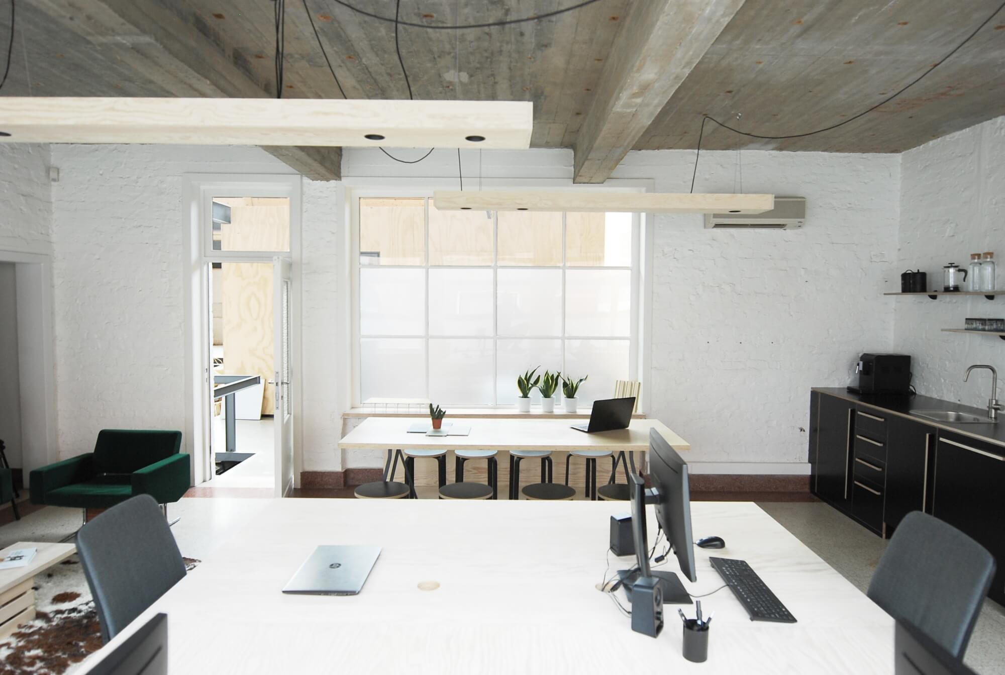 Architectural offices with white bricks, grey ceiling, and light plywood accents.