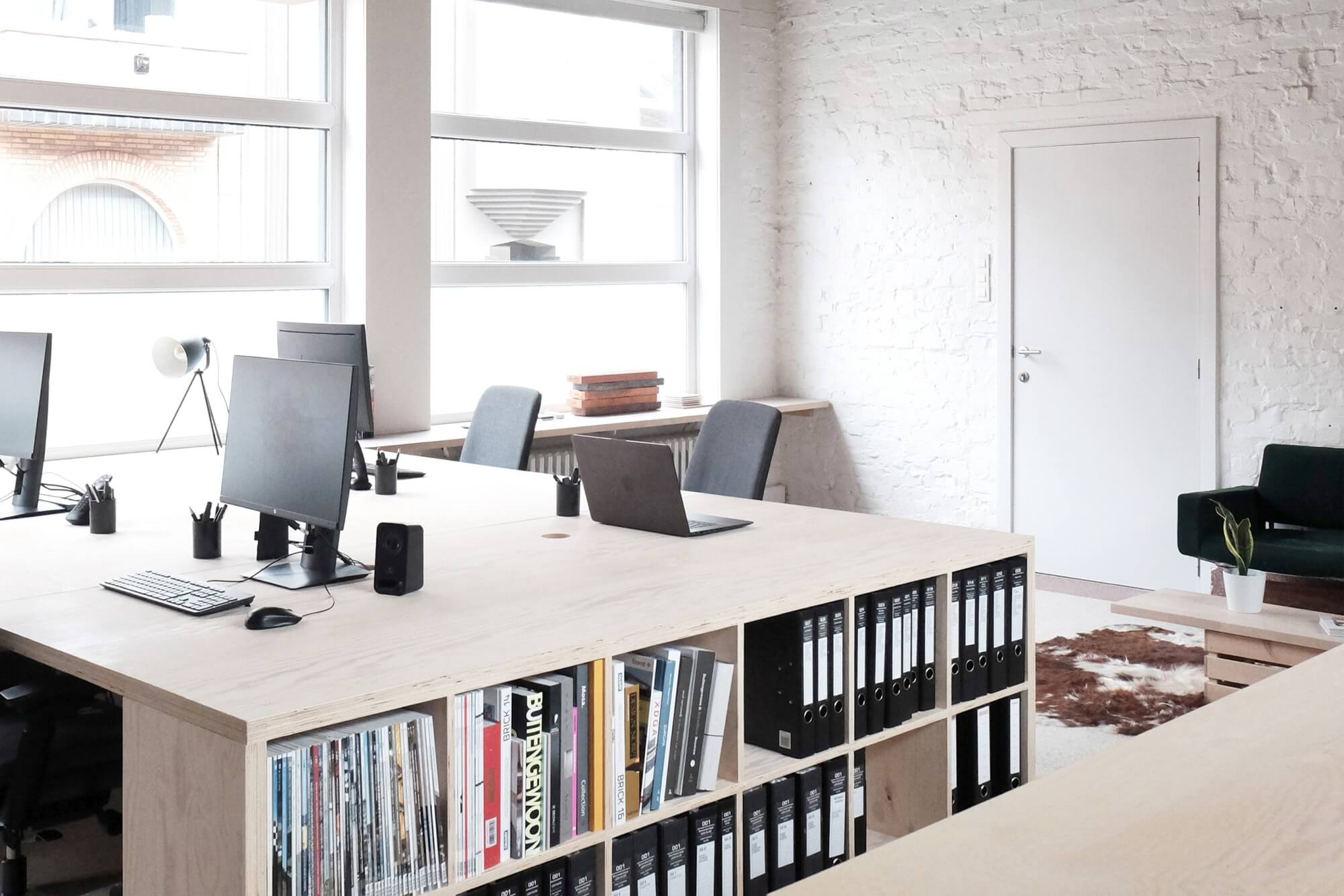Open office space with plywood bookshelves and desk.