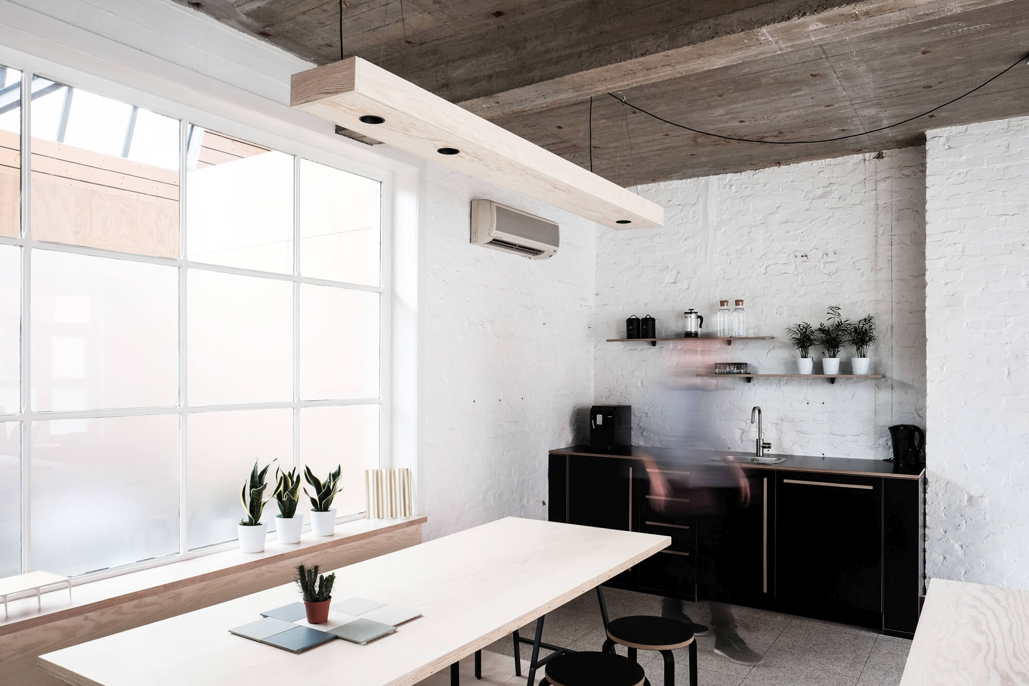 Architect office with white brick, plywood, and bold accents.