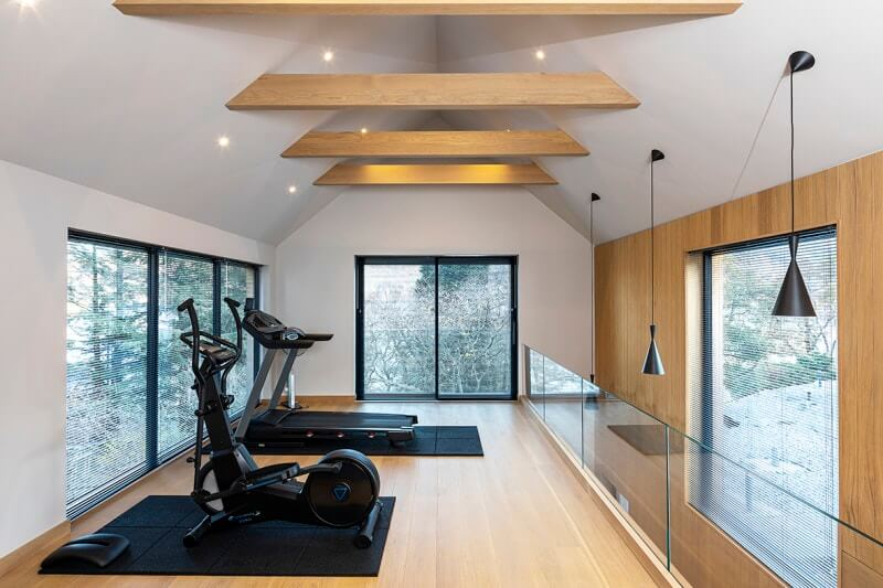 Fitness room with hardwood flooring, a wood accent wall, and faux wood beams.