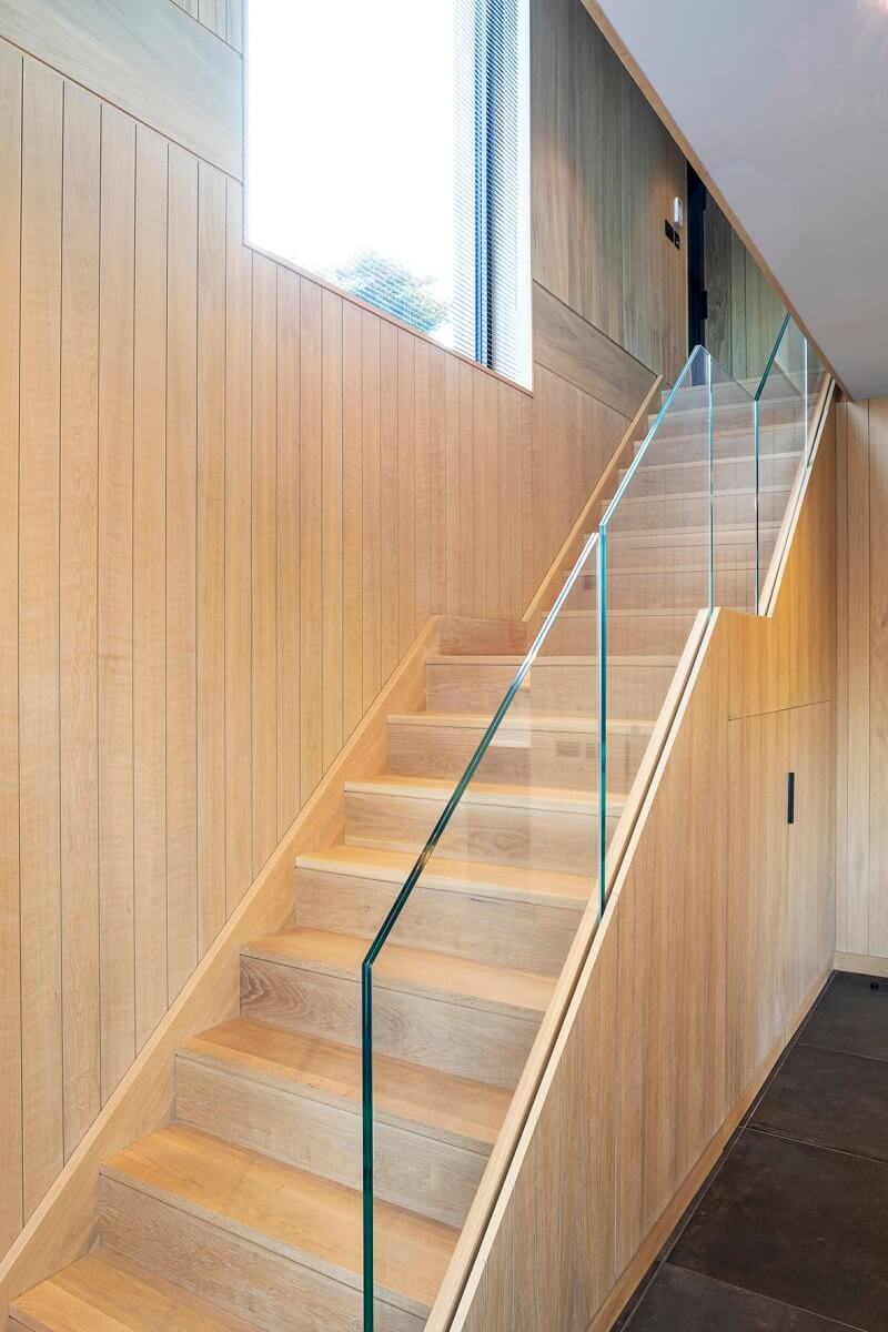 Wood staircase with wood paneling on the side and a glass banister and handrail.