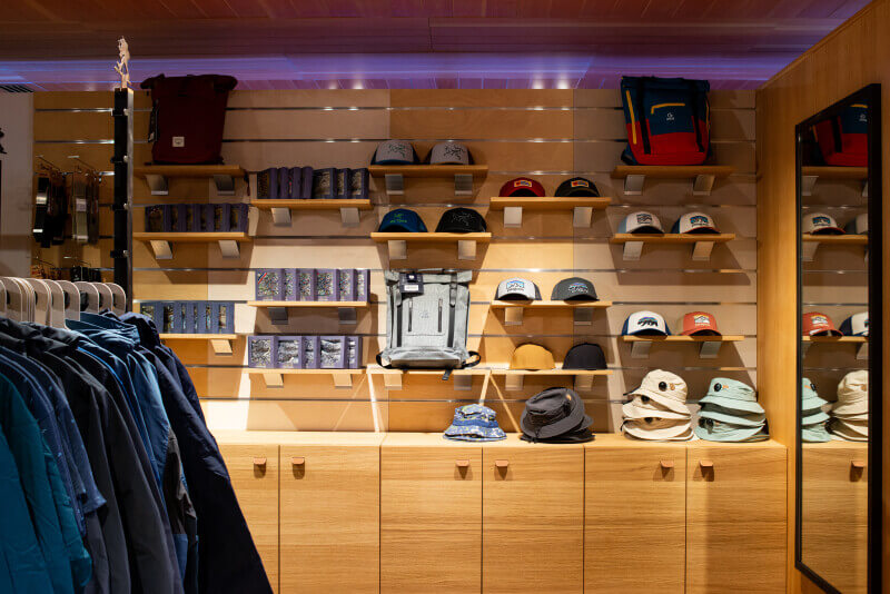 A wall in a store lined with wood displays that show hats, backpacks, and other items for sale.