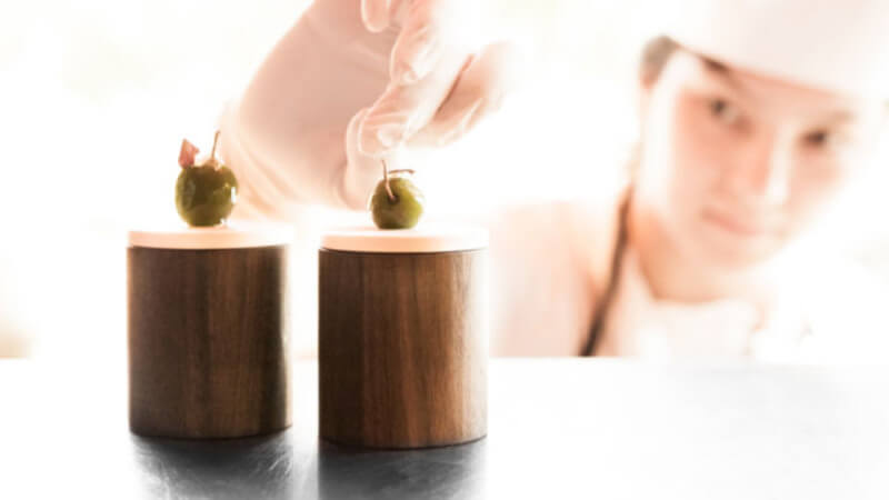 A chef placing olives on top of 2 round wooden serving utensils.