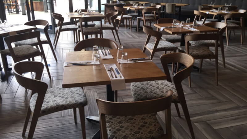 A restaurant with a herringbone style wood floor and wood tables throughout.