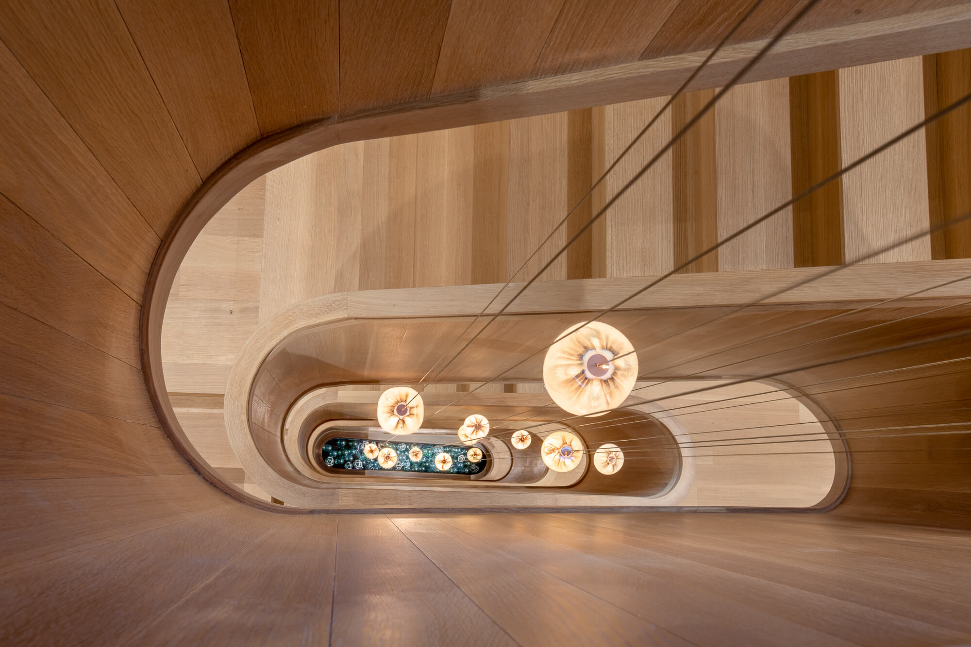 View down the middle of a spiraling wooden staircase.