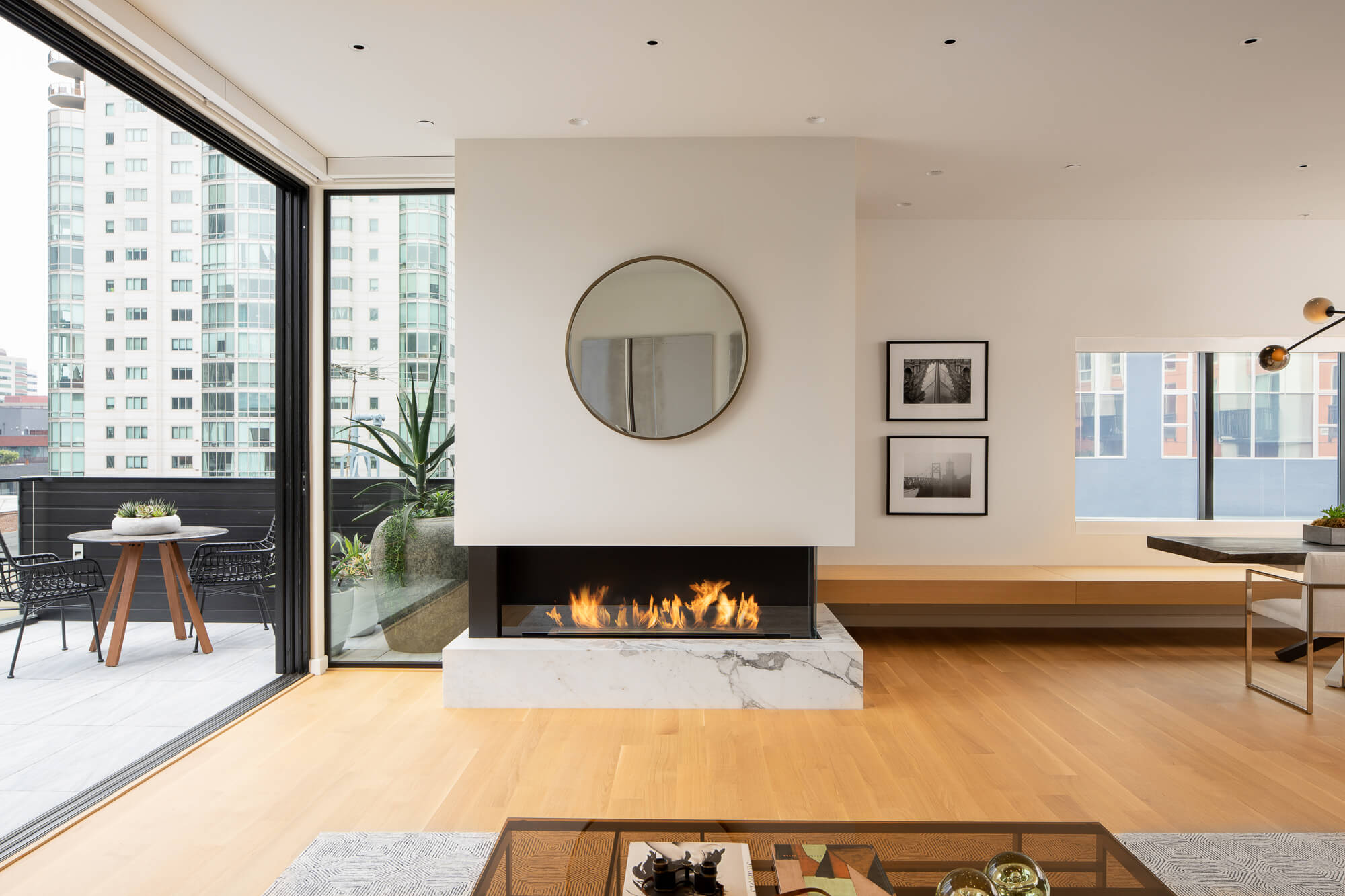 Living room with fireplace and floor to ceiling glass doors that are open, rift sawn white oak flooring.