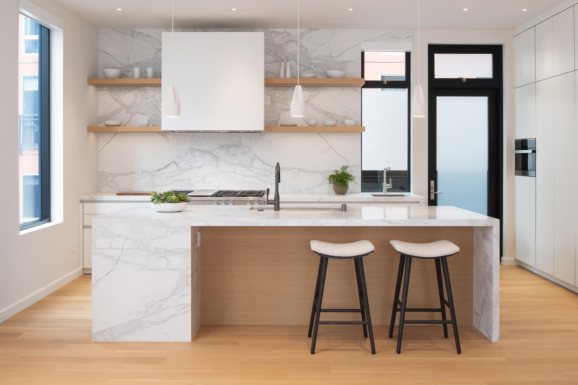 Light and clean kitchen with rift sawn white oak floors, marble island and backsplash, and floating shelving.