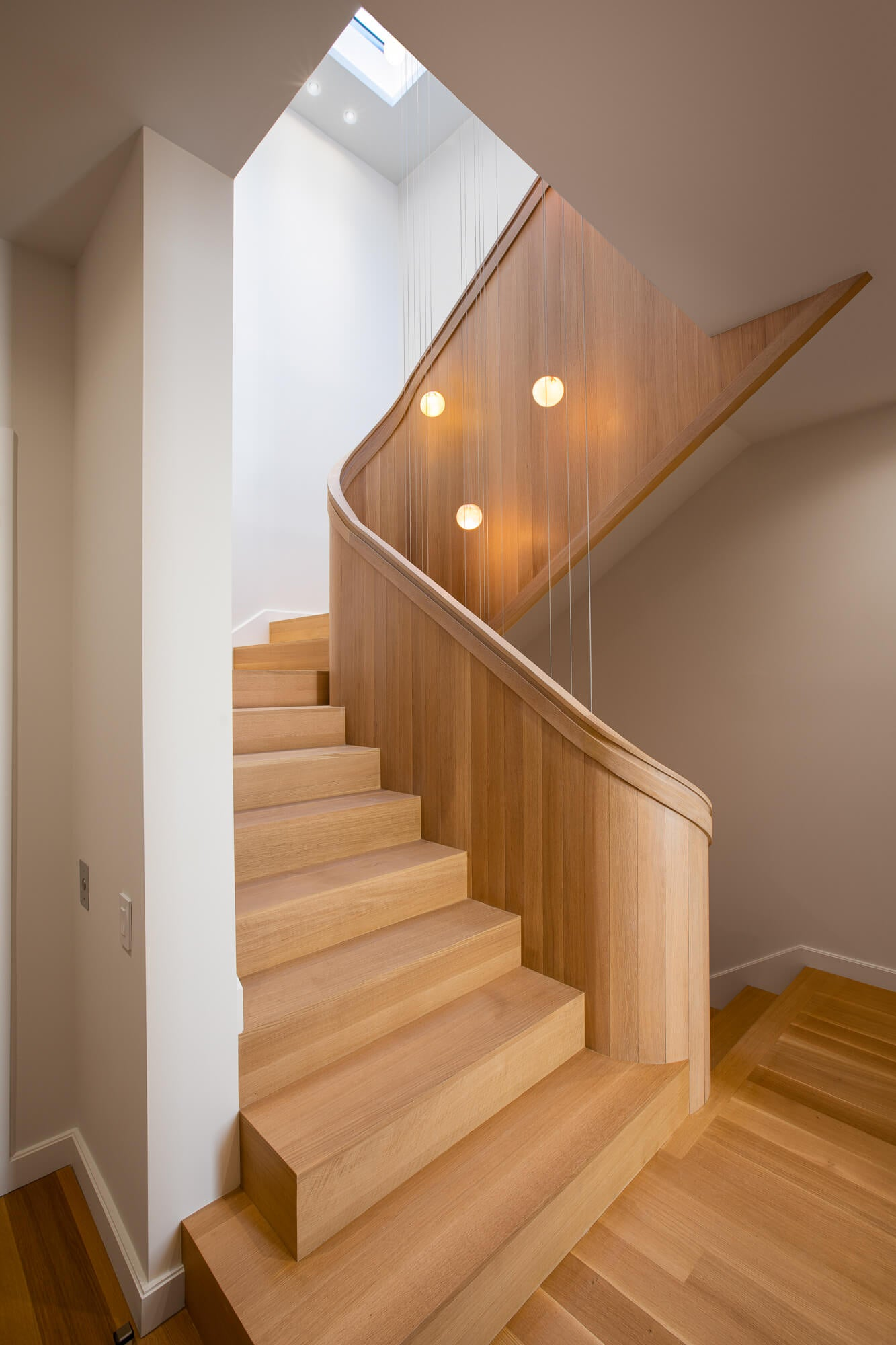 Beautiful rift sawn white oak spiraling staircase finished with Rubio Monocoat's oil based wood finish.