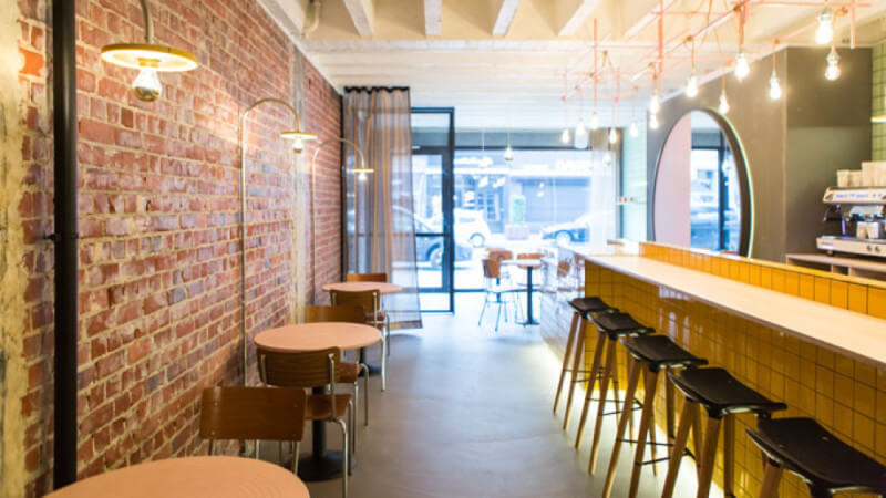 The inside of a long but small restaurant with bright color wood surfaces.