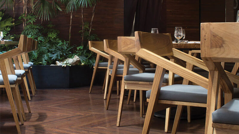 A line of wooden chairs in a restaurant finished with Rubio Monocoat Oil Plus 2C.