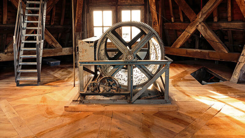 The music machine in the top of the cathedral spire, surrounded by wood flooring.