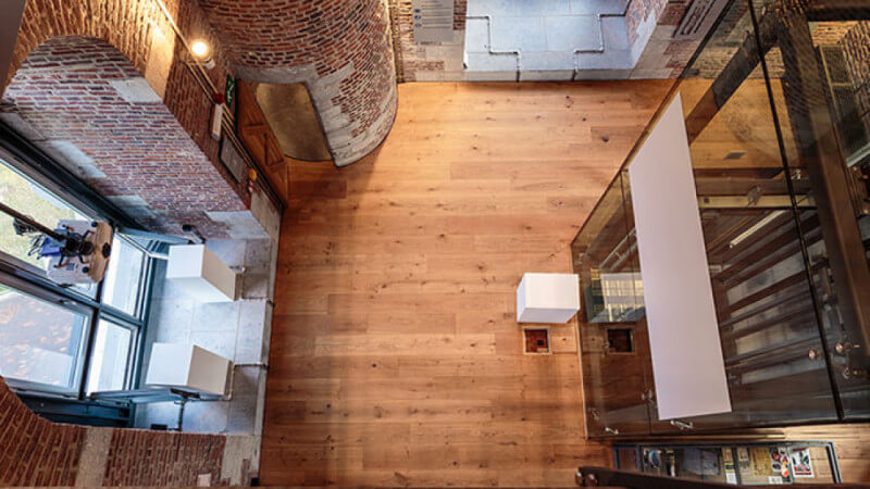 Looking down on the hardwood flooring of the Le Beffroi de Mons.