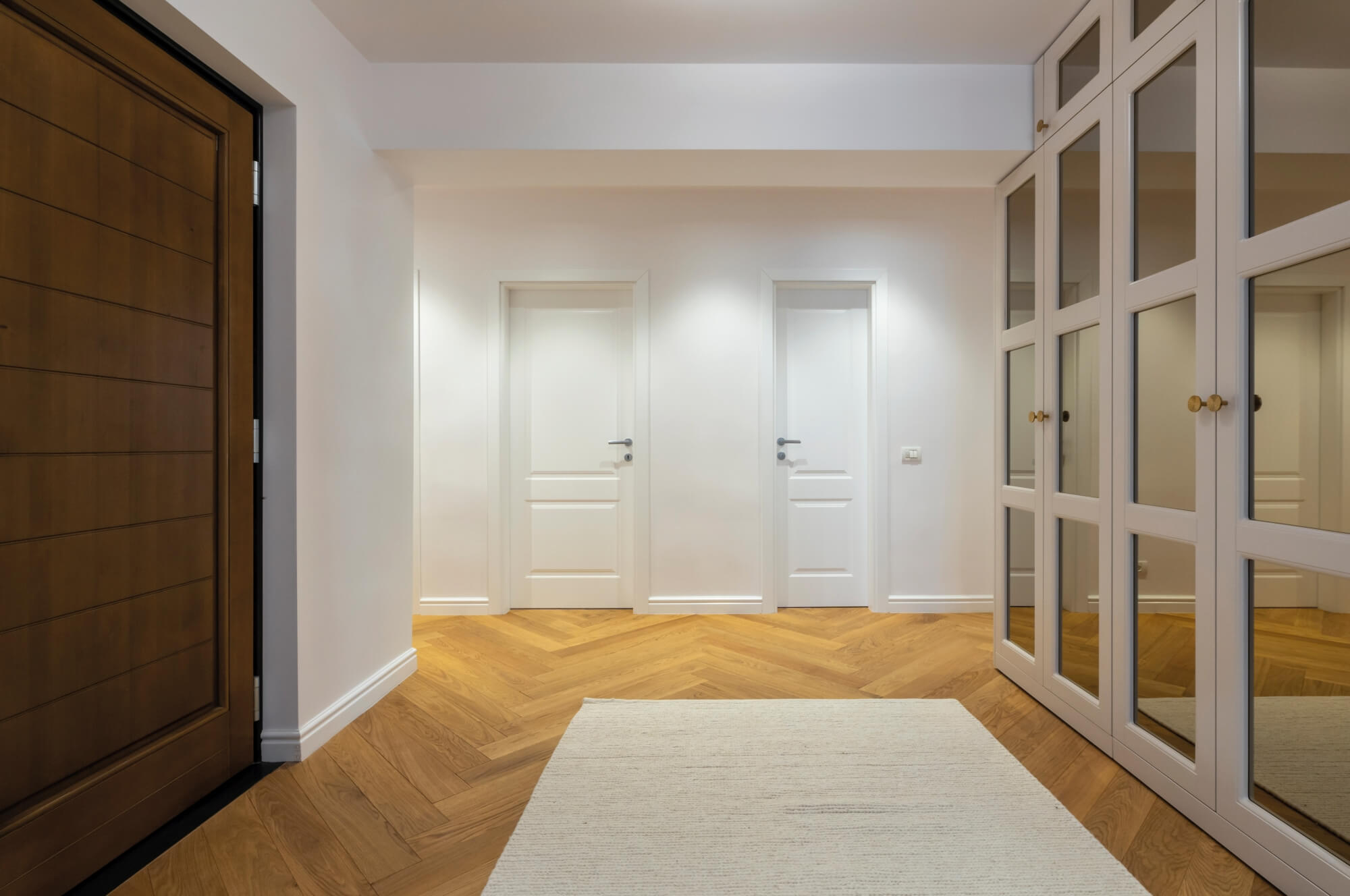 Large clean entry with herringbone flooring.