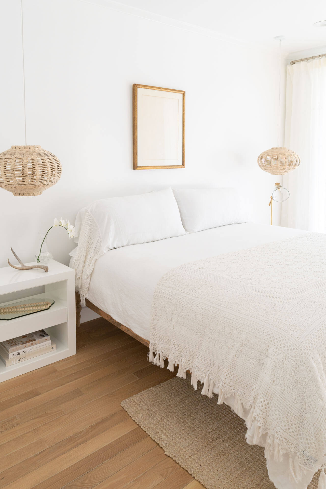 Guest bedroom with white decor and wood flooring