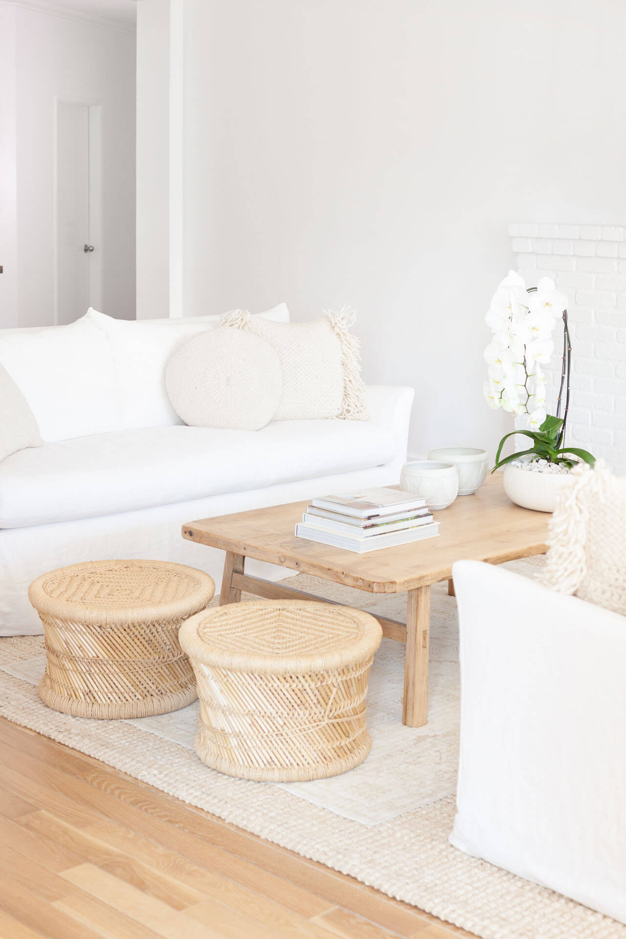 Natural looking wood coffee table between two white couches