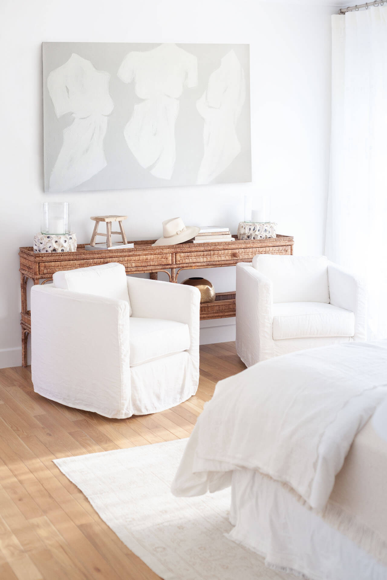 Guest bedroom with natural hardwood flooring and white decor