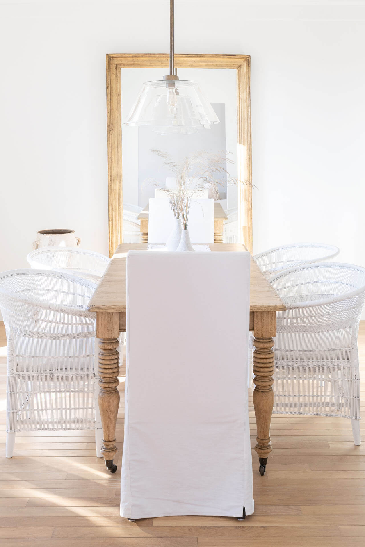 Natural wood dining table with white chairs and decor placed in front of a mirror