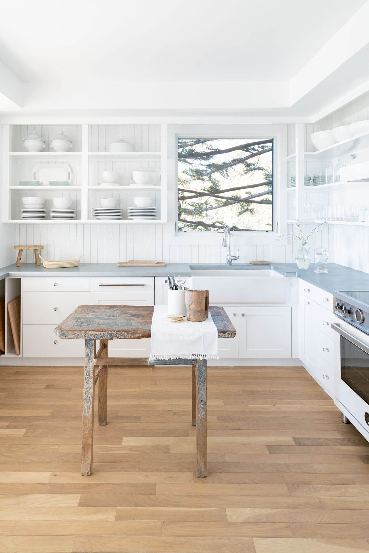 Light and airy kitchen with white cabinetry and natural hardwood flooring