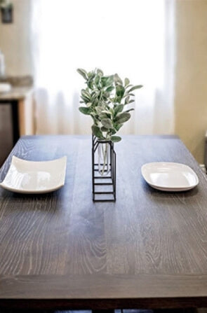 A wood dining table with 2 place settings and a plant in the middle.