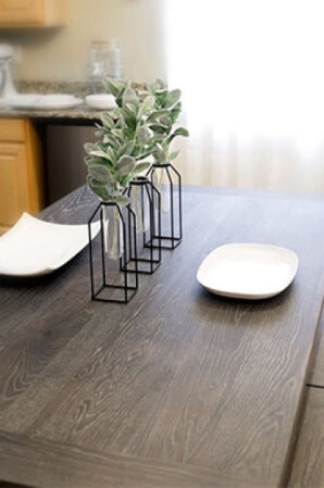 Farmhouse table top with dark wood and 2 place settings on it.