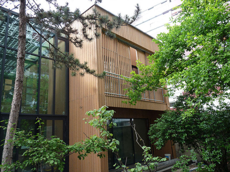 The exterior of a bed and breakfast that has wood cladding finished with an exterior wood oil and trees growing around the exterior.
