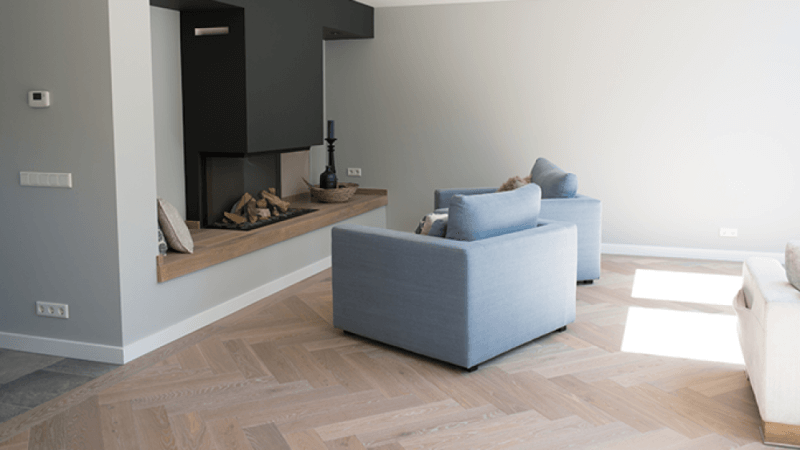 Herringbone hardwood flooring in a living area with a durable floor finish applied.