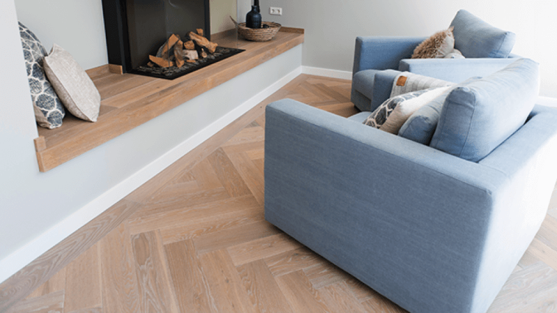 A classic herringbone wood floor with a light color floor finish on it.