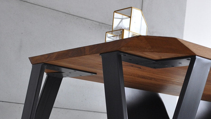 Modern wood table with geometric lines and metal legs.