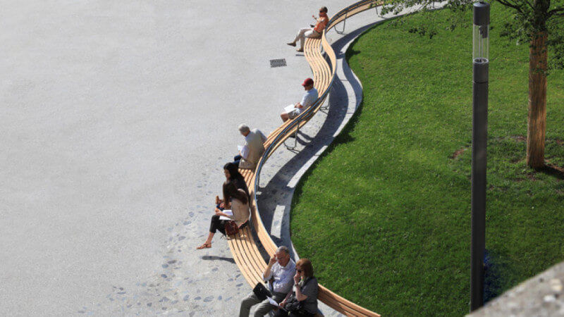 A wood bench curves around a green lawn and has people sitting on it.