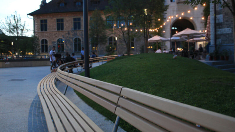 Close up image of wood benches curving around a lawn at night.