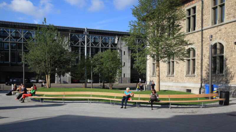 A wood bench with people sitting on it winds through a courtyard.