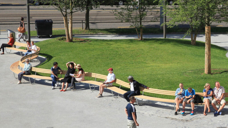 A curved wood bench with people sitting on it in front of a grass yard.