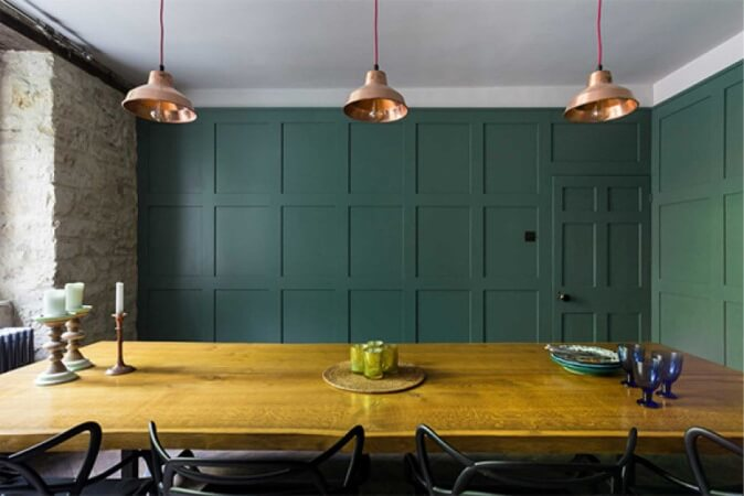 Live edge dining table in a room with paneled teal walls.