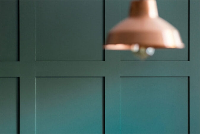 Close up of paneled teal wall with rose gold light fixture in foreground.