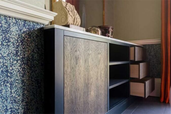 Modern dresser with wood paneling in front.