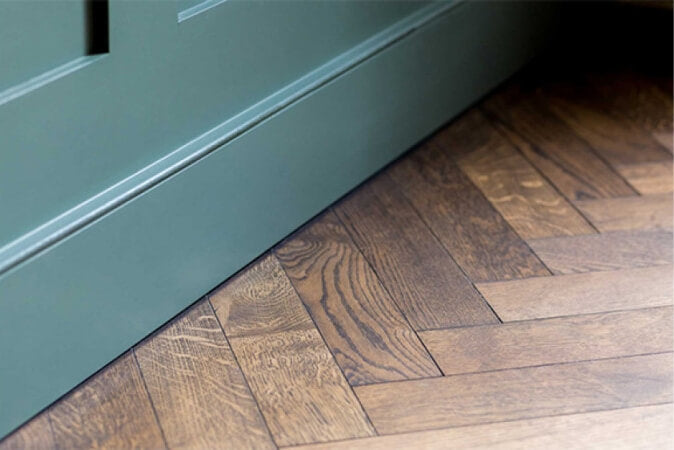 Dark oak herringbone hardwood flooring with teal teal.