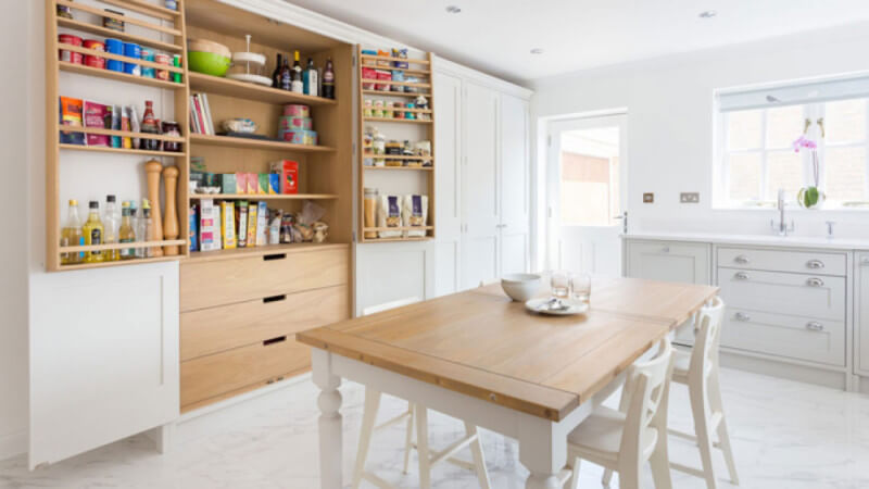 A beautifully redesigned shaker kitchen that takes advantage of natural light, fitted with natural wood shelving.
