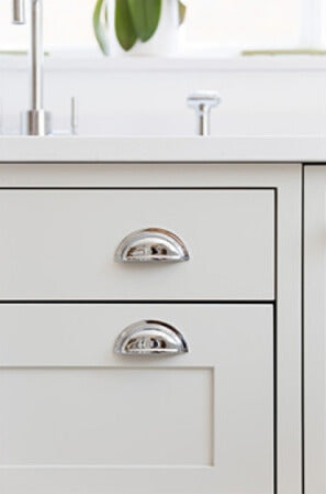 Drawer pulls on a white shaker cabinet.