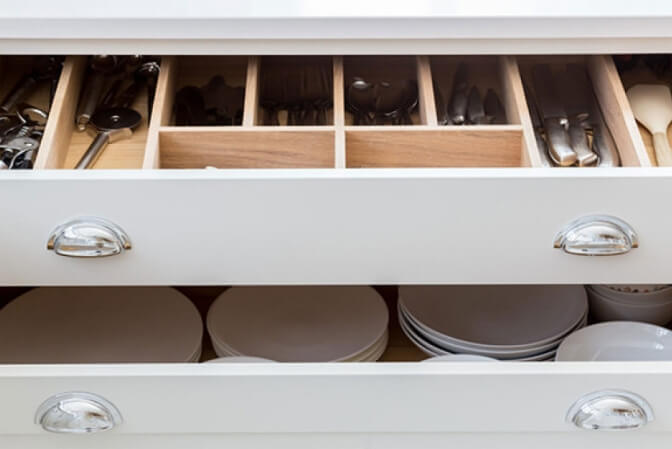 White shaker drawers with silverware organizer.