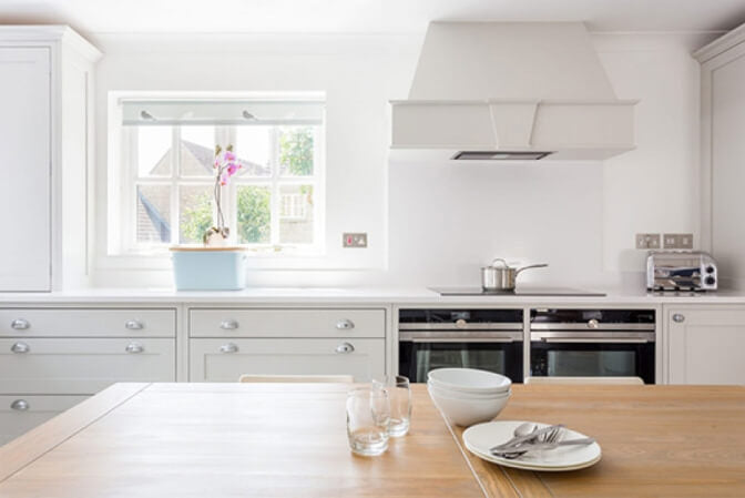 White shaker kitchen with natural wood table.