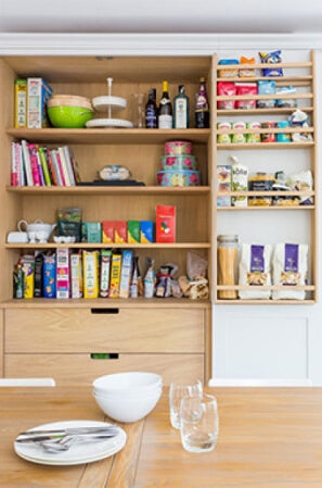 Wood pantry shelving in a white shaker kitchen cabinet.