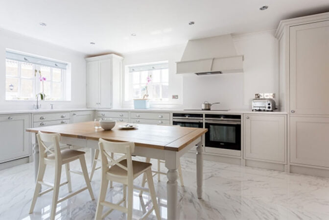White shaker kitchen with dining table in the middle.